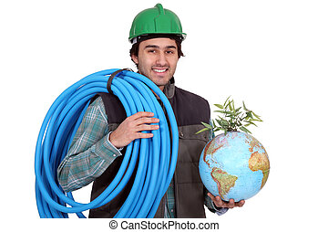 Construction worker holding corrugated tubing and a globe