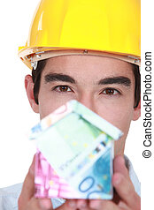 Construction worker holding house made from money