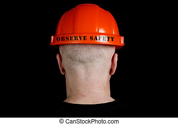 Construction worker in hard hat with an inscription observe...
