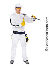 construction worker in white coveralls packs with a hammer and chisel on white wall
