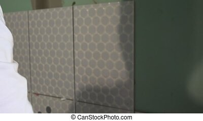 Construction worker install ceramic tile on wall. Focus...