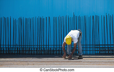 Construction worker installing binding wires to steel bars -...