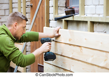 construction worker installing wooden planks on house facade