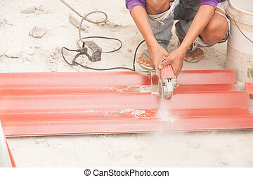 Construction worker is cutting tile roof