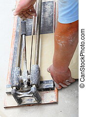 Construction worker is cutting tiles at home, renovation