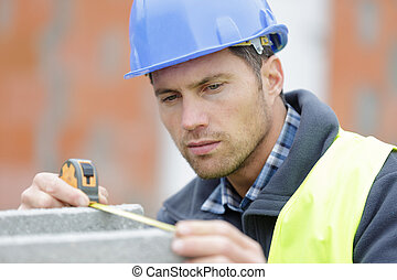 construction worker is measuring a cement block