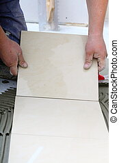 Construction worker is tiling at home, tile floor adhesive...