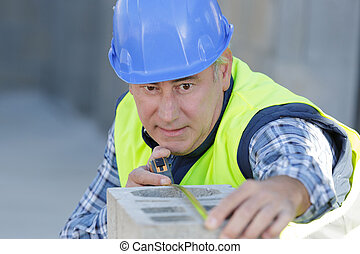 construction worker is working with cement block measurement