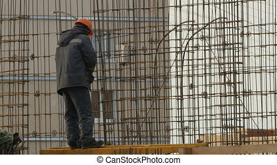 construction worker knits steel reinforcement of house walls, low angle of view