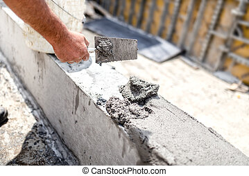 Construction worker leveling concrete with putty knife at building site. Details of construction industry