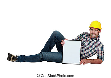 Construction worker lying down with a board left blank for your message