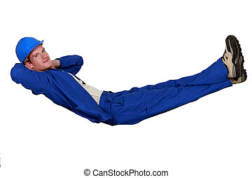 Construction worker lying in an imaginary hammock