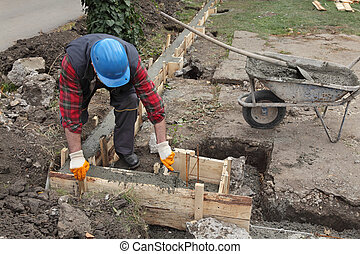 Construction worker making concrete foundation in formwork