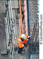 Construction worker making reinforcement in building site
