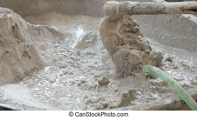 Construction worker mixing concrete with water for building....