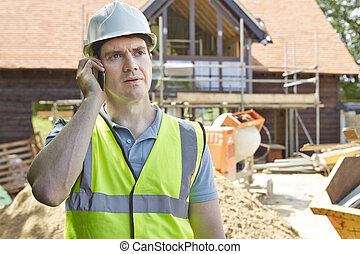 Construction Worker On Building Site Using Mobile Phone