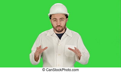 Construction worker on building site talking to camera on a Green Screen, Chroma Key.