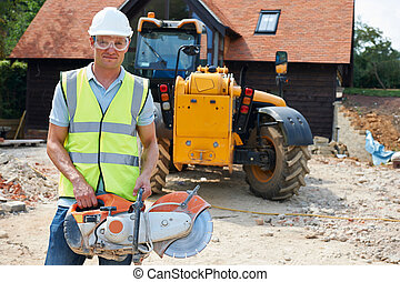 Construction Worker On Site Holding Circular Saw