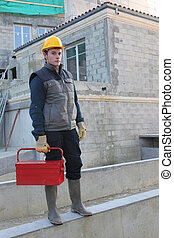 Construction worker on site with a toolbox
