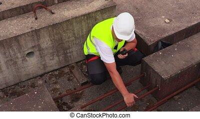 Construction worker on walkie talkie near concrete blocks