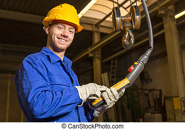 Construction worker operating crane in assembly hall - ...