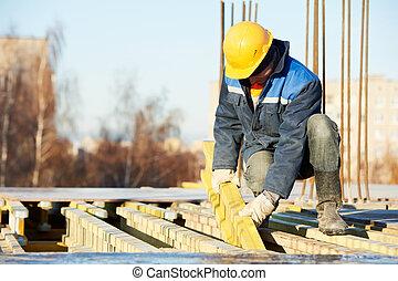 construction worker at construction site assembling falsework for concrete pouring