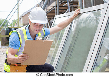 Construction Worker Preparing To Fit New Windows
