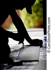 Silhouette of a construction worker measuring during a remodeling project in a home.