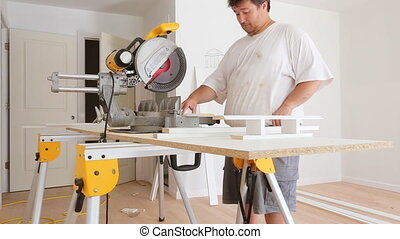 Construction worker remodeling home Carpenter cutting wooden...