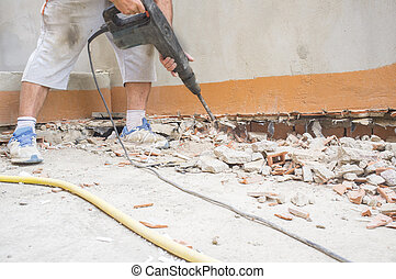 Construction worker removing burr from skirting board wall with jackhammer tool