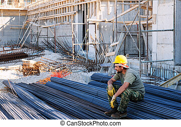 Construction worker resting on steel bars - Construction ...