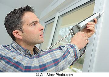 construction worker sealing window in house