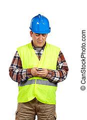 Construction worker sending sms