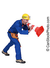 Construction worker shouting into a traffic cone