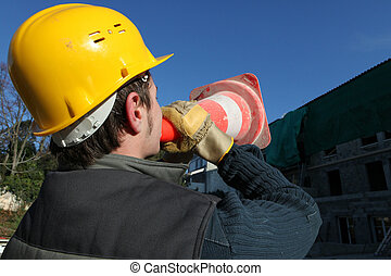 Construction worker shouting through cone