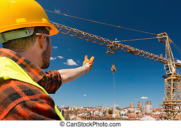 Construction worker signaling to crane operator