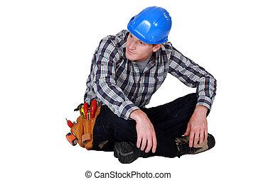 Construction worker sitting cross-legged