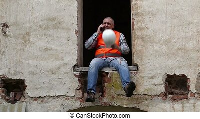 Construction worker sitting in wind