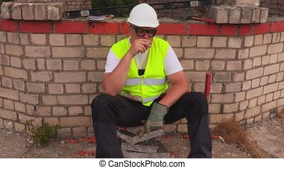 Construction worker smoking near unfinished building