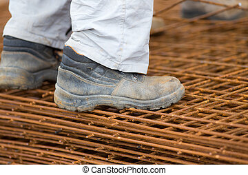 Construction worker standing on reinforcement mesh