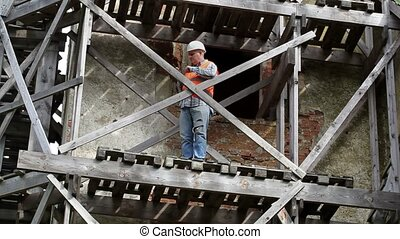 Construction worker standing on wooden scaffolding and using...