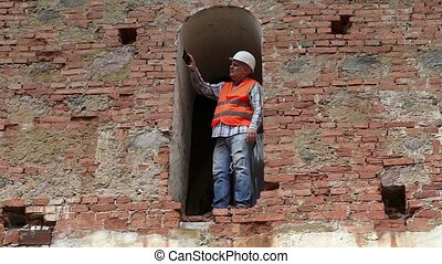 Construction worker take pictures on smarth phone near old wall