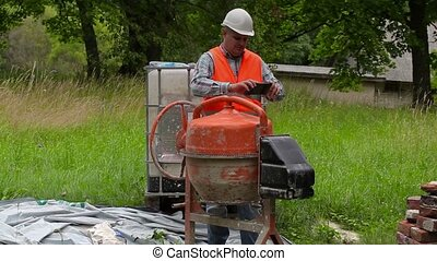 Construction worker take pictures on tablet PC near concrete mixer