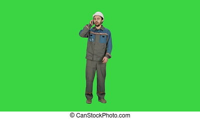 Construction Worker talk with Cell Telephone on a Green Screen, Chroma Key.