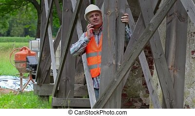 Construction worker talking on phone and looking through wood scaffolding