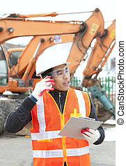 Construction worker talking on the phone and holding clipboard