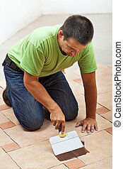 Construction worker testing the joint color on ceramic tiles floor - spreading it with a spatula