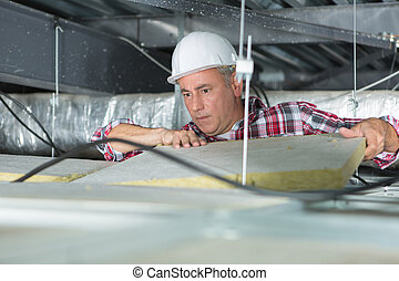 construction worker thermally insulating house attic with...