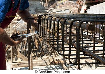 Construction worker ties reinforcing steel rebar. Close up