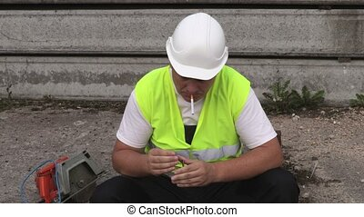 Construction worker trying to smoke